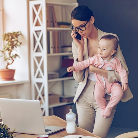 photo of mom holding baby while working