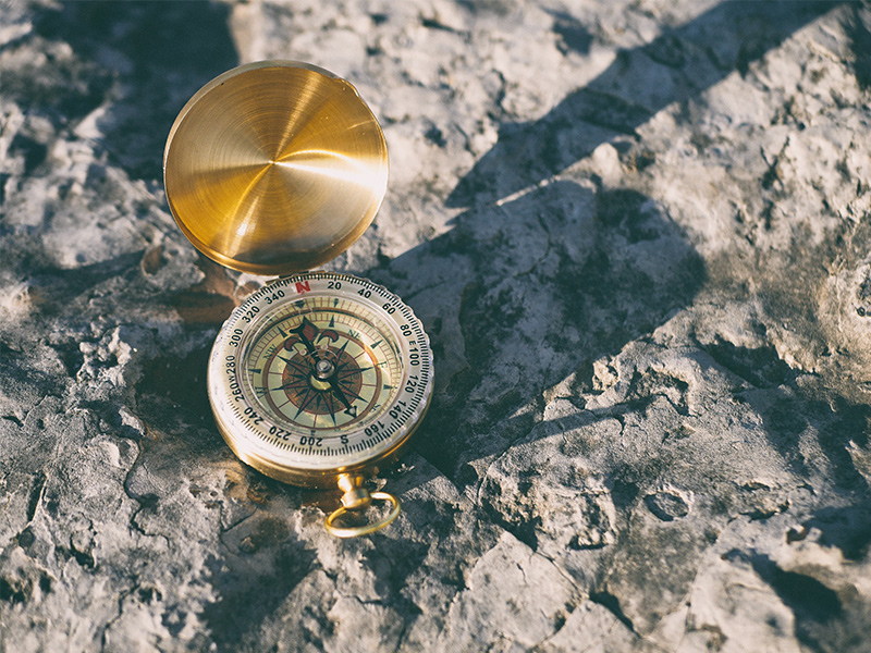 Open Compass On Top Of A Rock