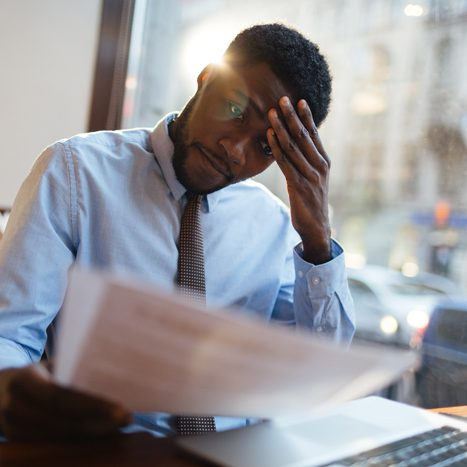 stressed looking man, reviewing papers