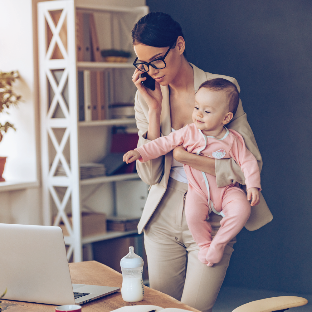 mother on phone holding baby reaching for computer
