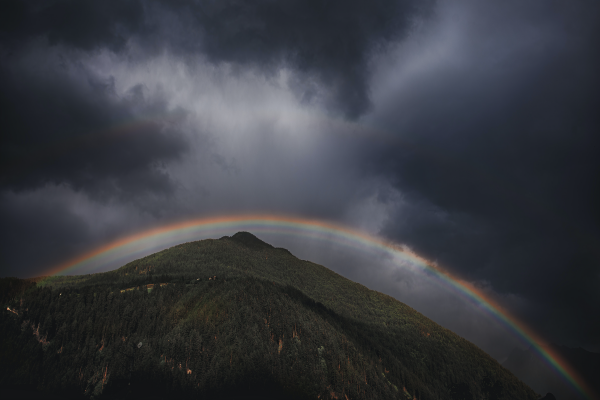 A Mountain Under A Dark Sky With A Rainbow Above It