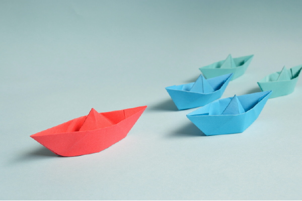 A Photo Of A Red Paper Boat Leading Three Blue Paper Boats