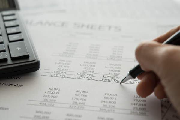 An Image Of Balance Sheets With A Calculator On Top