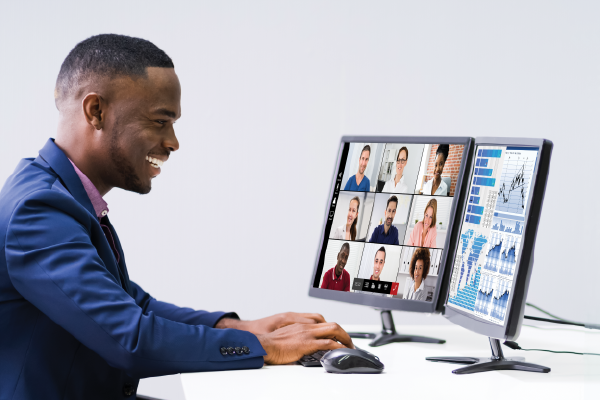 A Happy Person Looking At Two Computer Screens, One With A Video Conferencing Screen Showing Multiple Faces And One Showing Graphs Less Visible