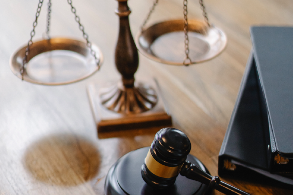 A Gavel Next To Binders And The Scales Of Justice