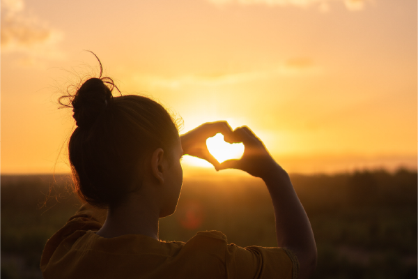 The Back Of A Person's Head Looking At A Golden Sunrise/sunset Making A Heart Shape With Their Hands Around The Glowing Sun, With Text Overlay That Says Webinars For Busy Lawyers Featuring Dr. Tracey Meyers, Psy.D., Under Her Bio Photo
