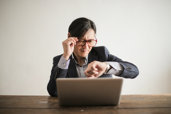 A Person Behind Their Laptop Grasping Their Glasses And Looking With Confusion At Their Watch