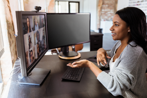 An Image Of A Person Seated In Front Of Two Computer Monitors, Speaking Over Video Conference On One