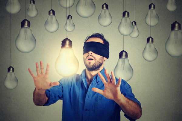 An Image Of A Blindfolded Person With Their Hands In The Air Near A Lit Lightbulb Surrounded By Many Dim Lightbulbs