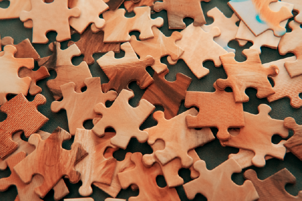 An Image Of Puzzle Pieces Unsorted In A Loose Pile