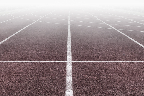 An Image Of Boundary Lines On A Track With Fog Ahead