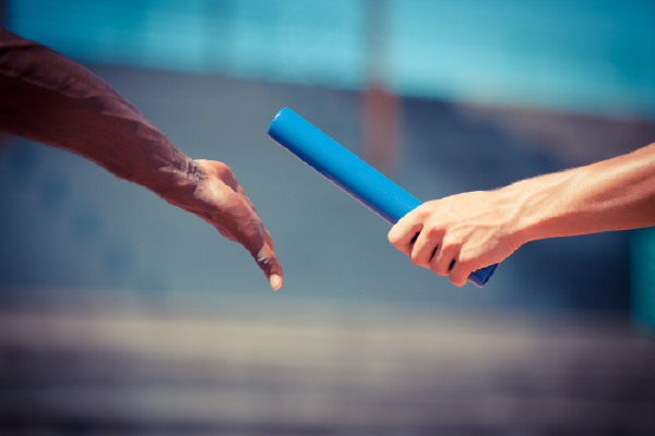 An Image Of A Relay Baton Being Handed Off From One Hand To Another