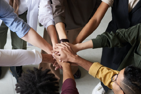 An Image Of The Hands Of A Diverse Circle Of 8 People Stacked All In The Center