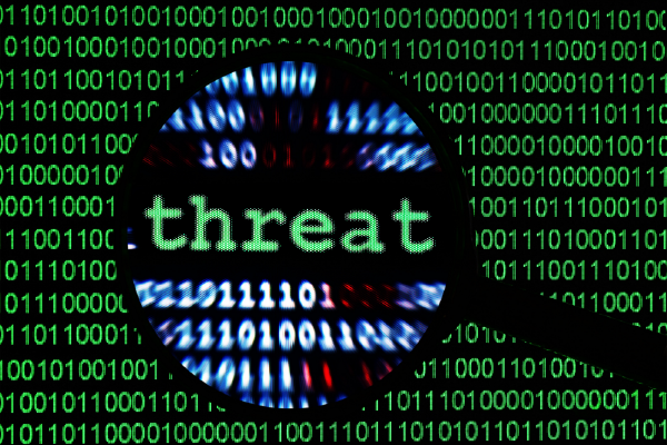 An Image Of The Word Threat In Focus Of A Magnifying Glass With Binary Code Lines Of 1s And 0s In The Background