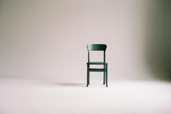 An Image Of An Empty Wooden Chair Against A Beige Wall On A Beige Floor