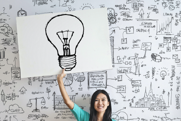 A Person In Front Of A Busy Whiteboard Holding A Drawing Of A Lightbulb Above Their Head